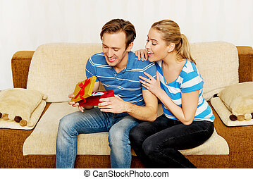 Young woman opening the gift she got from her boyfriend