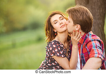 Loving couple on a meadow - Happy couple kissing on a green...