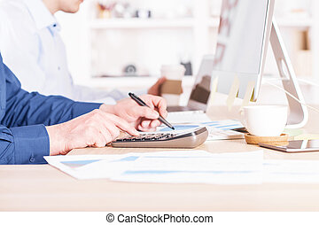 Man using calculator - Sideview of businessman using...