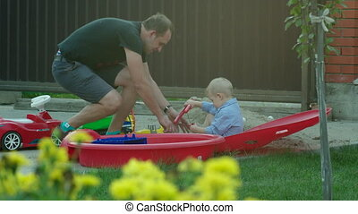 Father Helping the Son in Putting Shoe On - Little boy is...