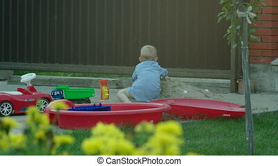 Boy Playing with Car in a Sandpit - Little boy is on the...