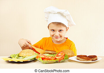 Young smiling boy in chef hat puts meat on hamburger - Young...