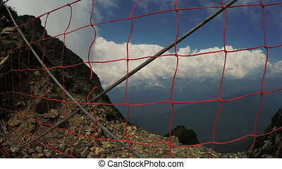 Security fencing in mountains - On edge of mountain cliff is...