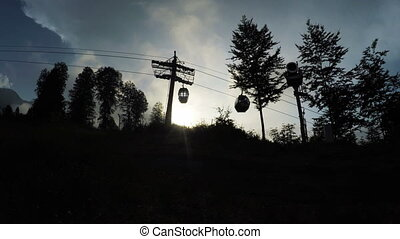 Ski lift Silhouettes backlit - Closed cabin ski lifts in...