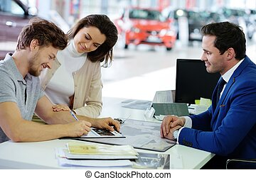 Happy young couple signing a contract to purchase a new car at the dealership showroom.