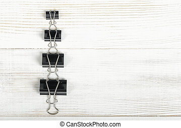 Black binder clips posted from the biggest to smallest on a...