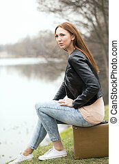 woman sitting on suitcase at the side of a river -...