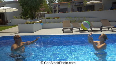 Man and woman playing ball in swimming pool in summer