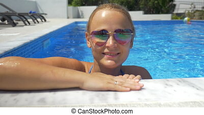Woman in sunglasses enjoying sunny day in the pool - Happy...