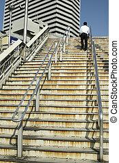 Man walking up stairs - Man walking up concrete stairs in...