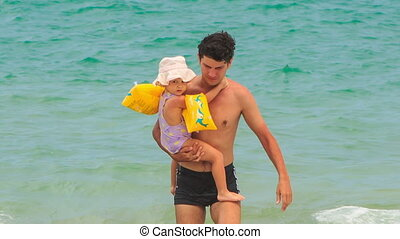 Father Carries Little Daughter from Azure Sea to Beach -...