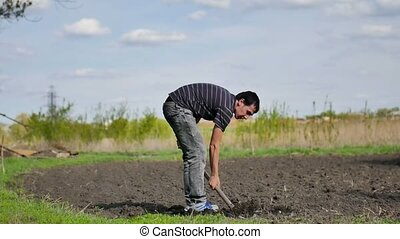 farmer man digs ground old dirty shovel on dry video ground...