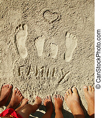 Family feet on the sand by the sea - a Family feet on the...