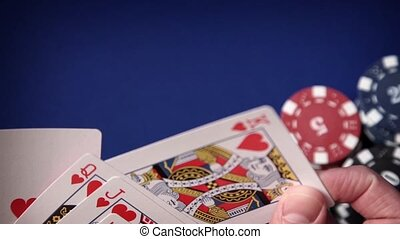 Royal flush in hand and gambling chips on casino blue felt -...