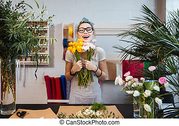 Happy woman florist with bunch of flowers standing and...