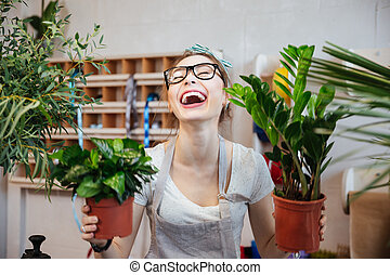 Happy woman florist holding plants in flowerpots and...