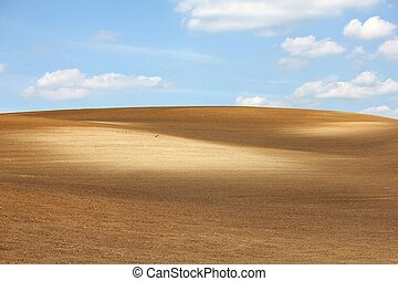 Brown arable hill against blue sky - Colorful brown arable...