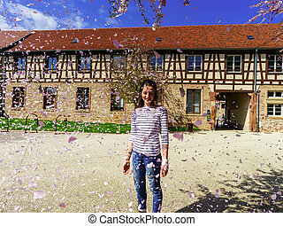 Teenage girl playing with falling petals on the sun, France