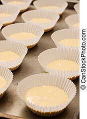 Rows of unbaked cup cakes lined up - Rows of raw dough cup...