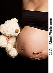 Young pregnant Caucasian woman holding teddy bear