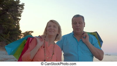 Mature couple relaxing with seaside walk after shopping