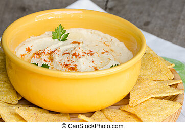 Hummus and corn chips, on wood table - Healthy homemade...