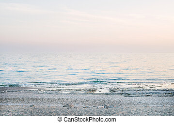 Peaceful scene of a calm sea at sunset, pastel colors