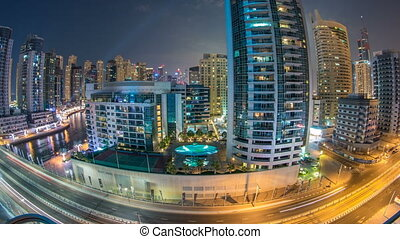 Dubai Marina at night timelapse with light trails of boats on the water and cars, Dubai, UAE