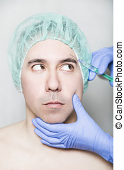 Doctor aesthetician makes face beauty injections to male...