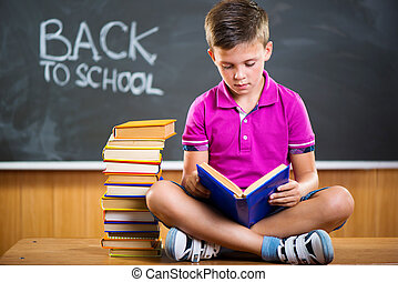 Cute school boy reading book in classroom against blackboard