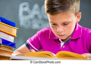 Cute schoolboy reading in classroom