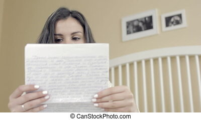 Young girl reading a letter smiling - Young girl reading a...