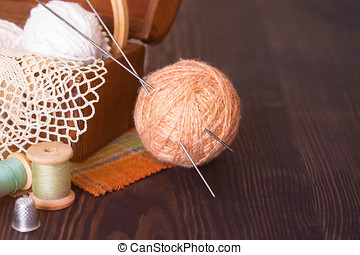 Casket with needlework and beige skein of thread with spokes...