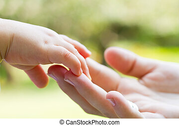 mother and babys hands - a mother tenderly holding her babys...