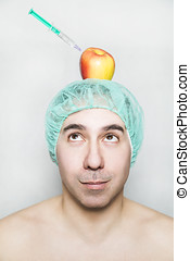 Apple with hyaluronic acid syringe on head of patient -...
