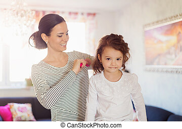 Mother combing hair of her daughter in the morning -...