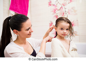 Mother combing hair of her daughter after taking bath -...