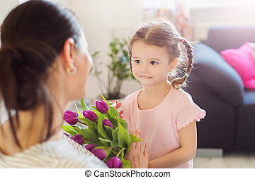 Mothers day, little girl giving flowers to her mum