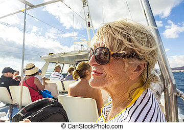 happy elderly woman enjoys the boat trip at the canary...