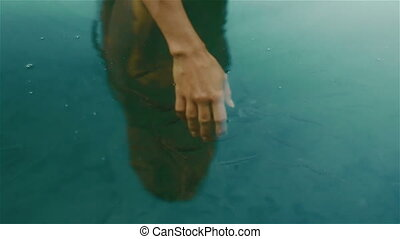 Fragile white woman hand submerged in the calm blue water of...