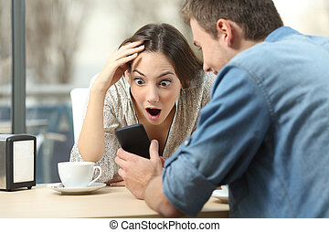 Surprised woman watching media in a smart phone - Surprised...