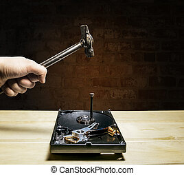 A hammer hits a nail into the hard drive from the computer...
