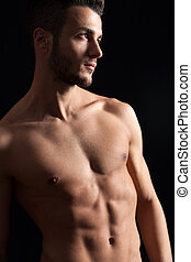 Shirtless young man against black background