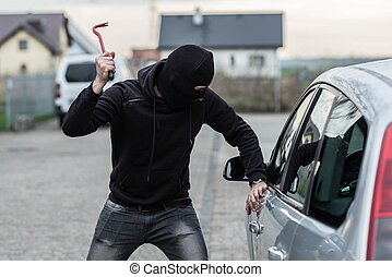Car thief breaking a glass in car with crowbar - Man dressed...