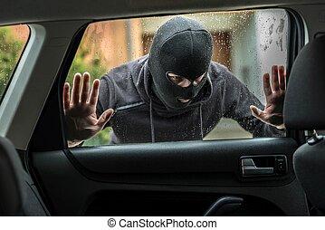 Car thief looking through car window - Man dressed in black...