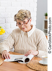 Relax with a newspaper and a cup of coffee - Senior woman in...