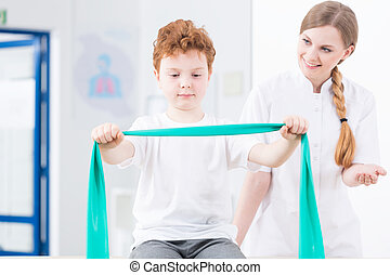 Physical therapist exercising with boy - Young pretty...
