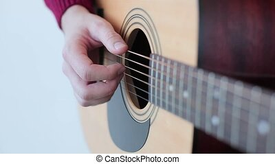 Man playing an acoustic guitar close up