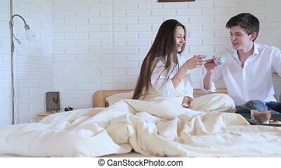 Couple drinking tea in bed in the loft room