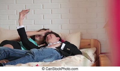 Couple doing selfie lying on the bed